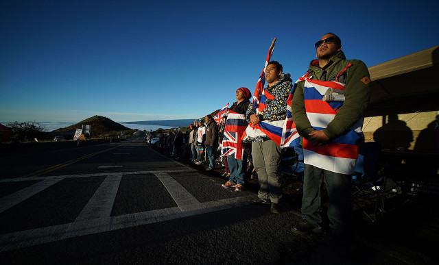 Flag draped Mauna Kea supporters bathe in the sunrise. 10 april 2015. photograph Cory Lum/Civil Beat