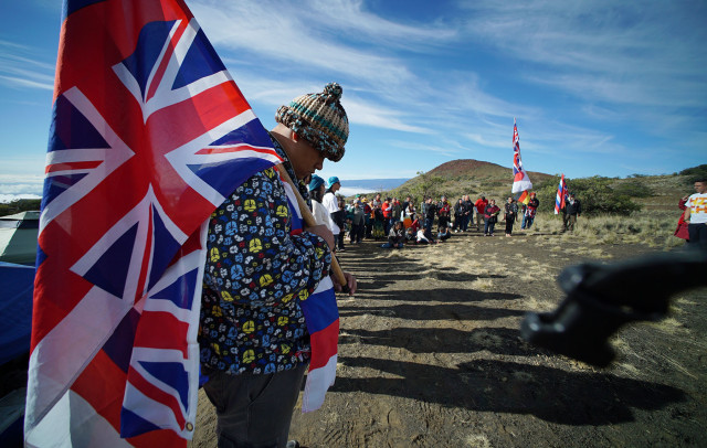 Big Island resident Kalae Kauwe draped in Hawaiian flags as hula halau dance near the Mauna Kea visitors center. 10 april 2015. photograph Cory Lum/Civil Beat