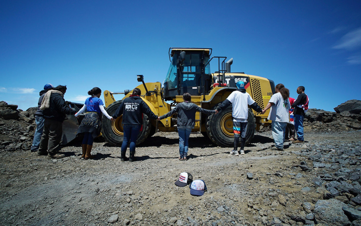 Kahookahi Kunuha leads a small group of supporters near a tractor on the TMT site on the summit of Mauna Kea on April 10, 2015.0 april 2015. photograph Cory Lum