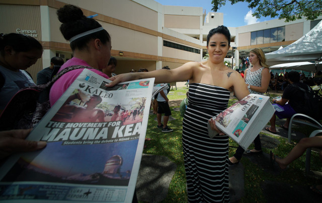 Kaleo O Hawaii Advertising representative Ashley Maria hands out today's University of Hawaii at Manoa newspaper to students during Mauna Kea rally held fronting the Campus Center. 13 april 2015. photograph Cory Lum/Civil Beat.