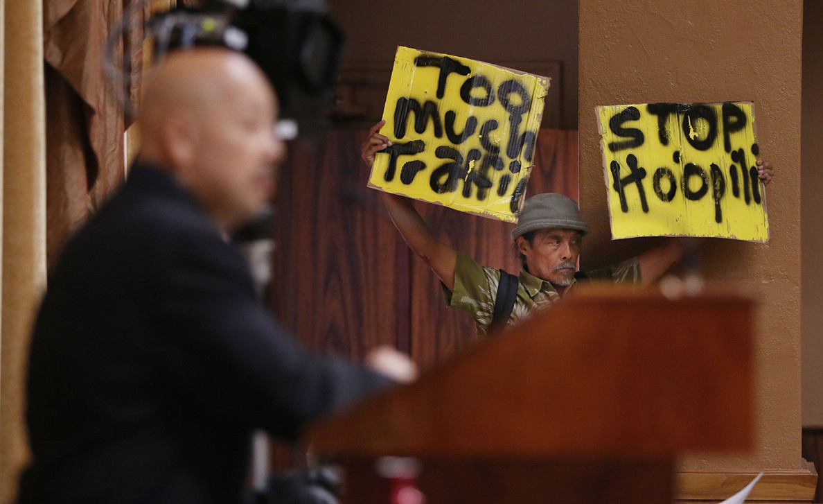Demonstrator holds sign during Honolulu City council hearing on Hoopili development. 6 may 2015. photograph by Cory Lum/Civil Beat