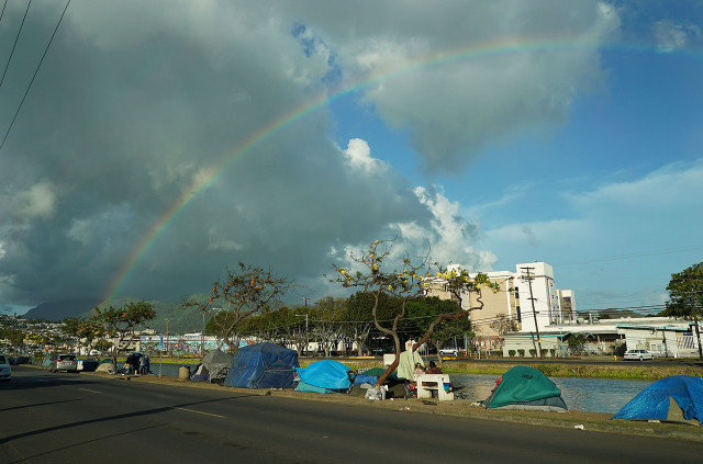 Tents and other belongings along the banks of the Kapalama Canal fronting a fleeting rainbow. 19 may 2015. photograph Cory Lum/Civil Beat