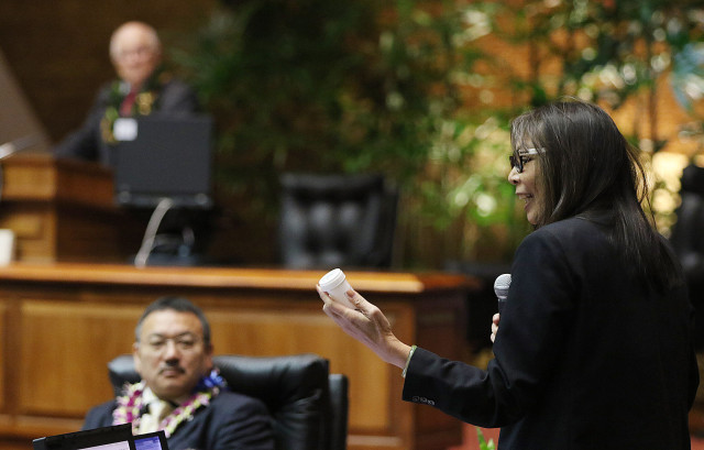 Representative Joy San Buenaventura holds up medical marijuana container and packaging on the floor of the house.  15 may 2015. photograph Cory Lum/Civil Beat