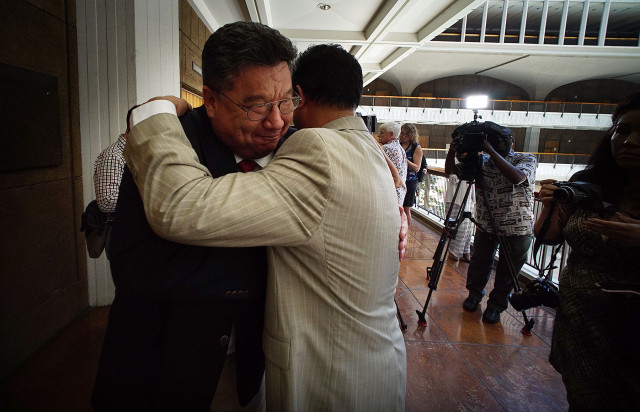 New Senate President Donald Kouchi is embraced by Rep Matcus Oshiro after press conference on 2nd floor of the Capitol. 5 may 2015. photograph Cory Lum/Civil Beat