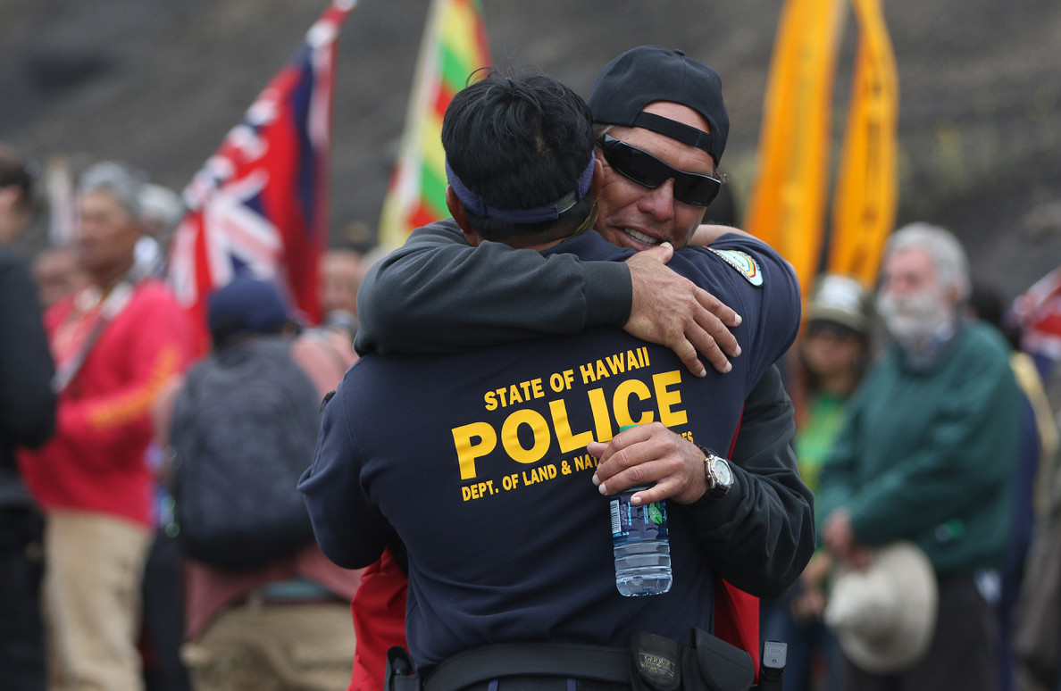 A protester and a DLNR law enforcement officer hug after the announcement that the motorcade is turning around Wednesday.