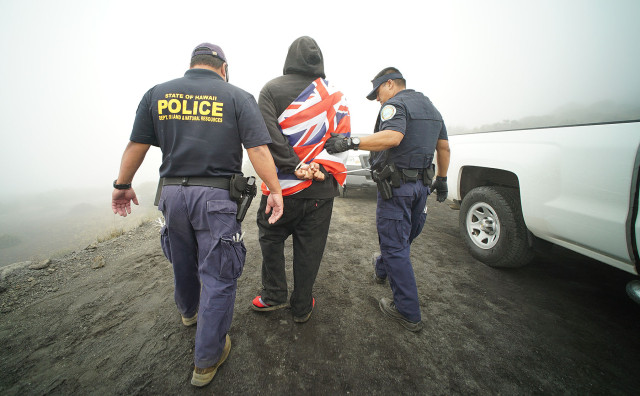 DLNR officers escort a handcuffed Hawaiian flag-draped demonstrator to an awaiting van containing other arrested protestors. Maunakea. Hawaii. 24 june 2015. photograph Cory Lum/Civil Beat
