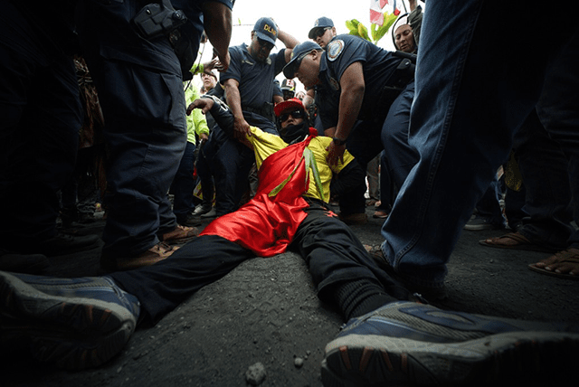 Law enforcement officers arrest a demonstrator on Mauna Kea on June 24.