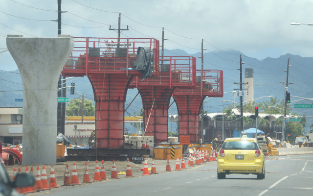 Rail guideway columns along Farrington Highway with view of the Waipahu Sugar Mill at right as construction moves eastward. 21 july 2015. photograph Cory Lum/Civil Beat