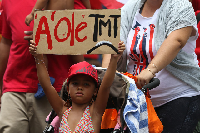 The next generation of demonstrator holds sign while being pushed in stroller along Kalakaua Ave during the Aloha Aina Unity March. 9 aug 2015. photograph by Cory Lum/Civil Beat