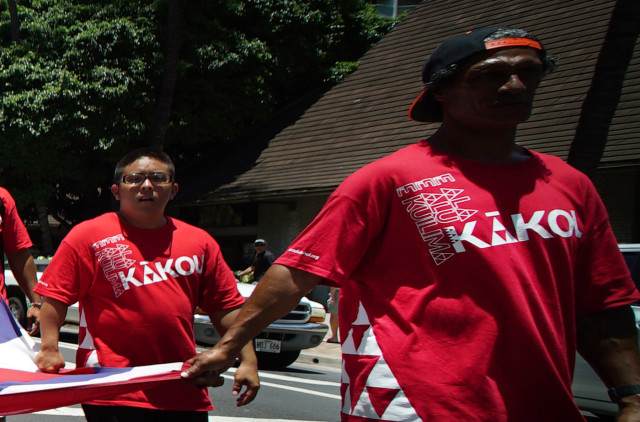 Aloha Aina marchers wearing Ala Alu Kuilima shirts holding flag. 10 aug 2015. photograph Cory Lum/Civil Beat