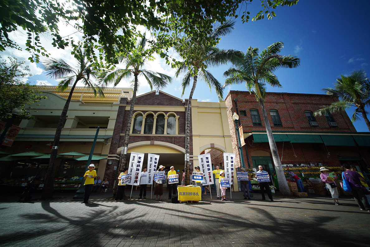 About a dozen sign-waving people spend their Sunday morning on a Kekaulike Street sidewalk to demonstrate their support for Hawaii residents who are among hundreds of practitioners of Falun Gong worldwide who have filed suit against former Chinese leader Jiang Zemin.