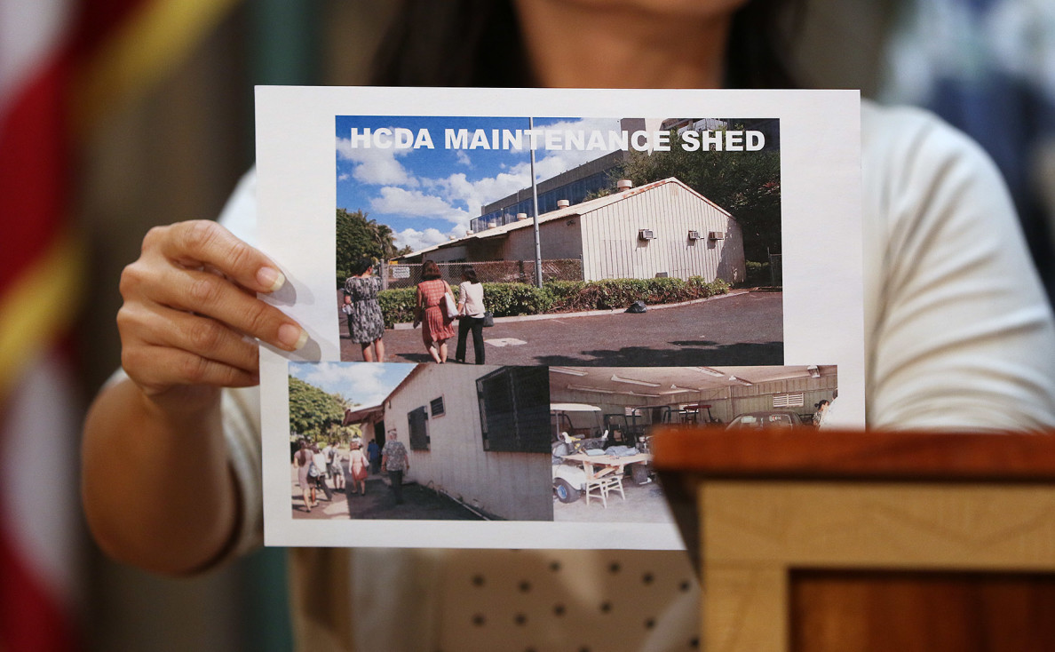 Luke holds a photo of a Hawaii Community Development Authority shed that might be converted to a temporary shelter for up to 40 people, one of several ideas under consideration.