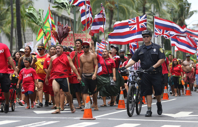 A lone HPD officers walks next to Aloha Aina Unity March demonstratos along Kalakaua Avenue. 9 aug 2015. photograph by Cory Lum/Civil Beat