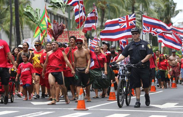 A lone HPD officers walks next to Aloha Aina Unity March demonstratos along Kalakaua Avenue. 9 aug 2015. photograph by Cory Lum/Civil Beat
