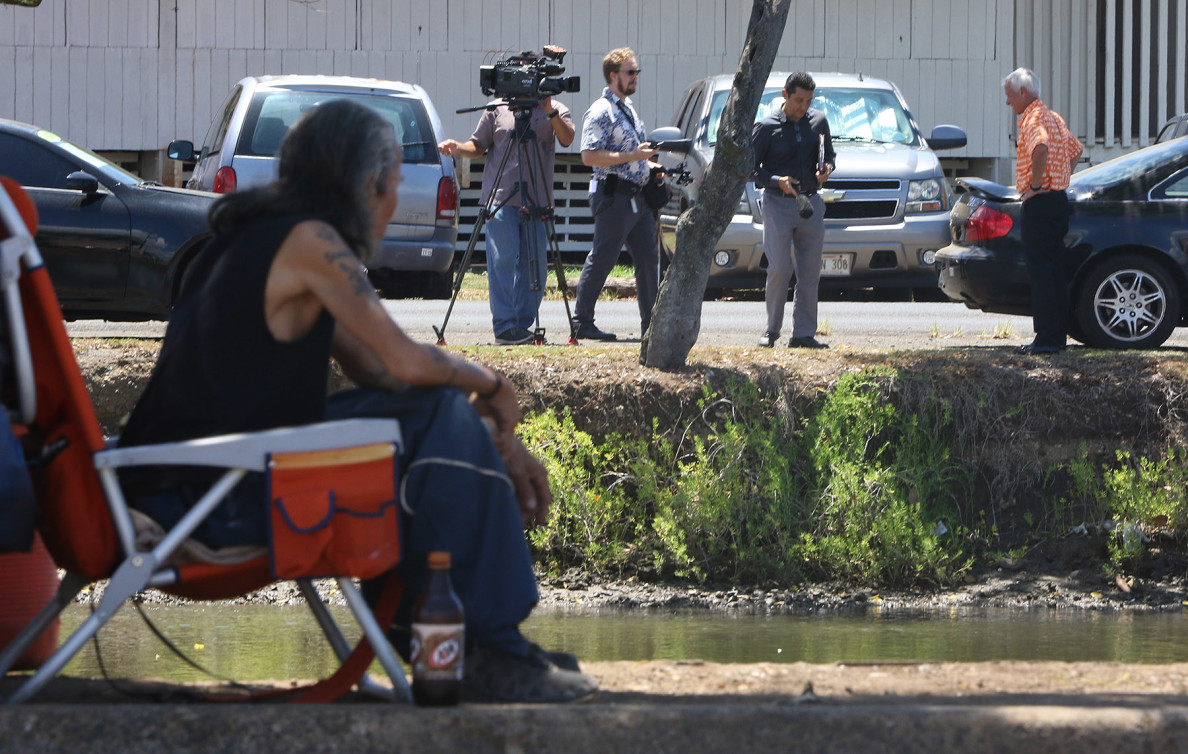 A homeless man watches from across Kapalama Canal as Mayor Kirk Caldwell, right, prepares to explain to reporters why he is signing a bill to ban camping or putting up tents along city-owned streams.