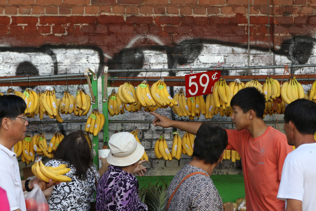 Buyers jostle for ripe bananas for sale on the Kekaulike Mall. Chinatown. Honolulu. 16 aug 2015. photograph Cory Lum/Civil Beat