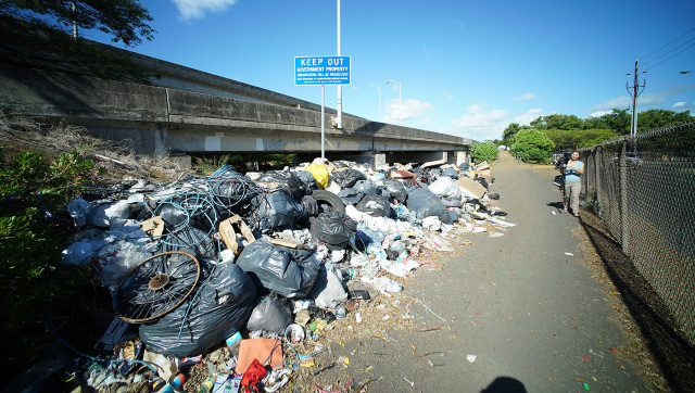 Large pile of fermenting and rotting trash along and under the Nimitz highway next to refuse collection center. 12 aug 2015. photograph Cory Lum/Civil Beat