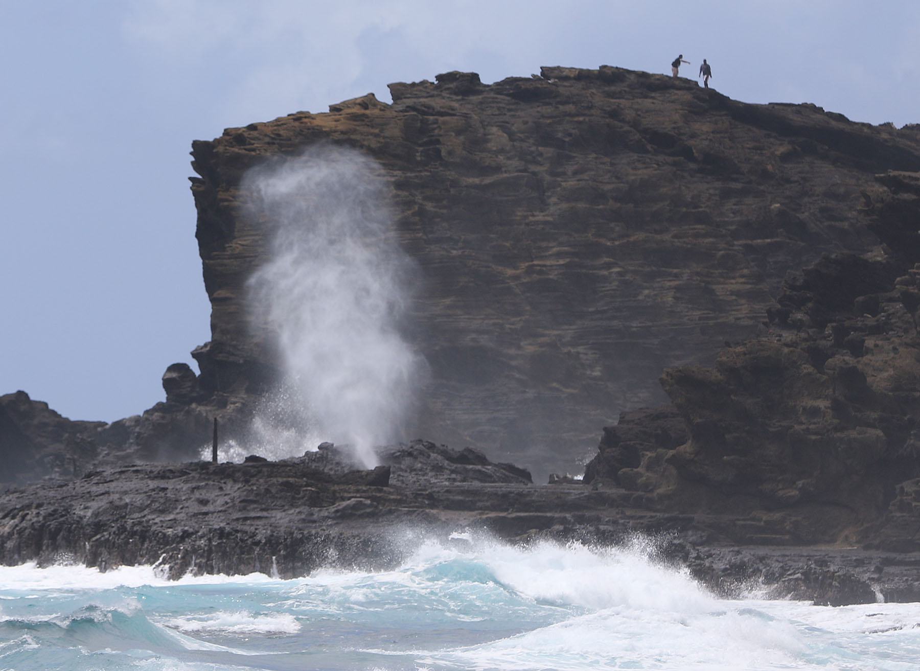 <p>Ignoring signs warning people to stay behind a fence, visitors climb the cliffs at Oahu&#8217;s Halona Blowhole.</p>