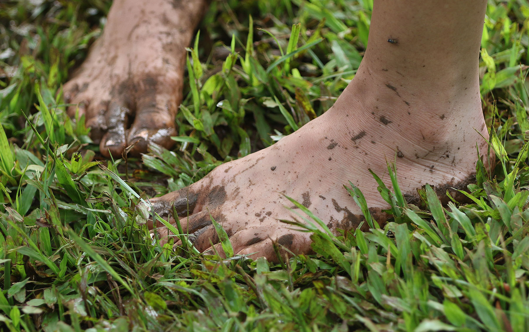 <p>One of the visitors to Ho&#8217;oulu &#8216;Aina Nature Park goes barefoot in muddy grass.</p>