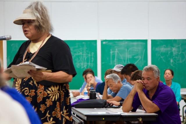 HELCO President Jay Ignacio, right, listens as Big Island resident Lei Kalamau testifies before the PUC.
