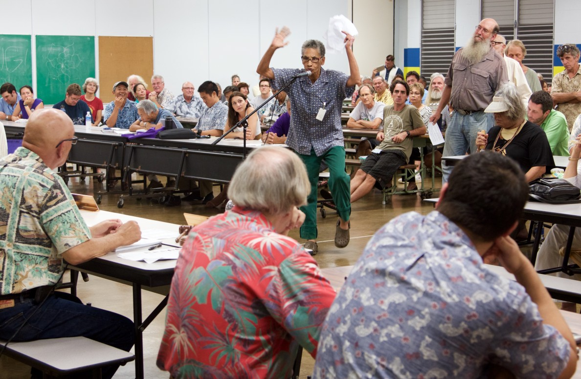 Big Island resident RJ Hampton tells the Public Utilities Commission to investigate NextEra Energy during a public hearing about the company's proposed merger with Hawaiian Electric, Tuesday, at Hilo High School.