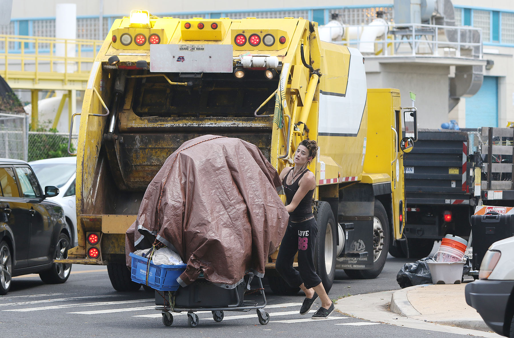 <p>A woman pushes away a cart loaded with belongings as the crew begins its work Monday in Kakaako.</p>