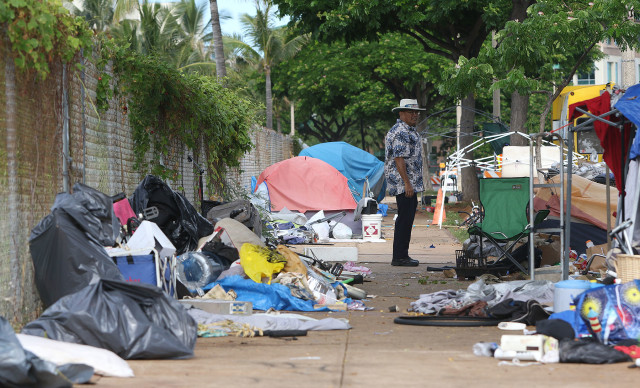 Honolulu Police Officer walks thru the cleared camping area as city workers ready for sweep along Ilalo Street. Another HPD colleague warned us about hyperdermic needles being found and also warned about walking thru the area along Ilalo Street. 8 oct 2015. photograph Cory Lum/Civil Beat
