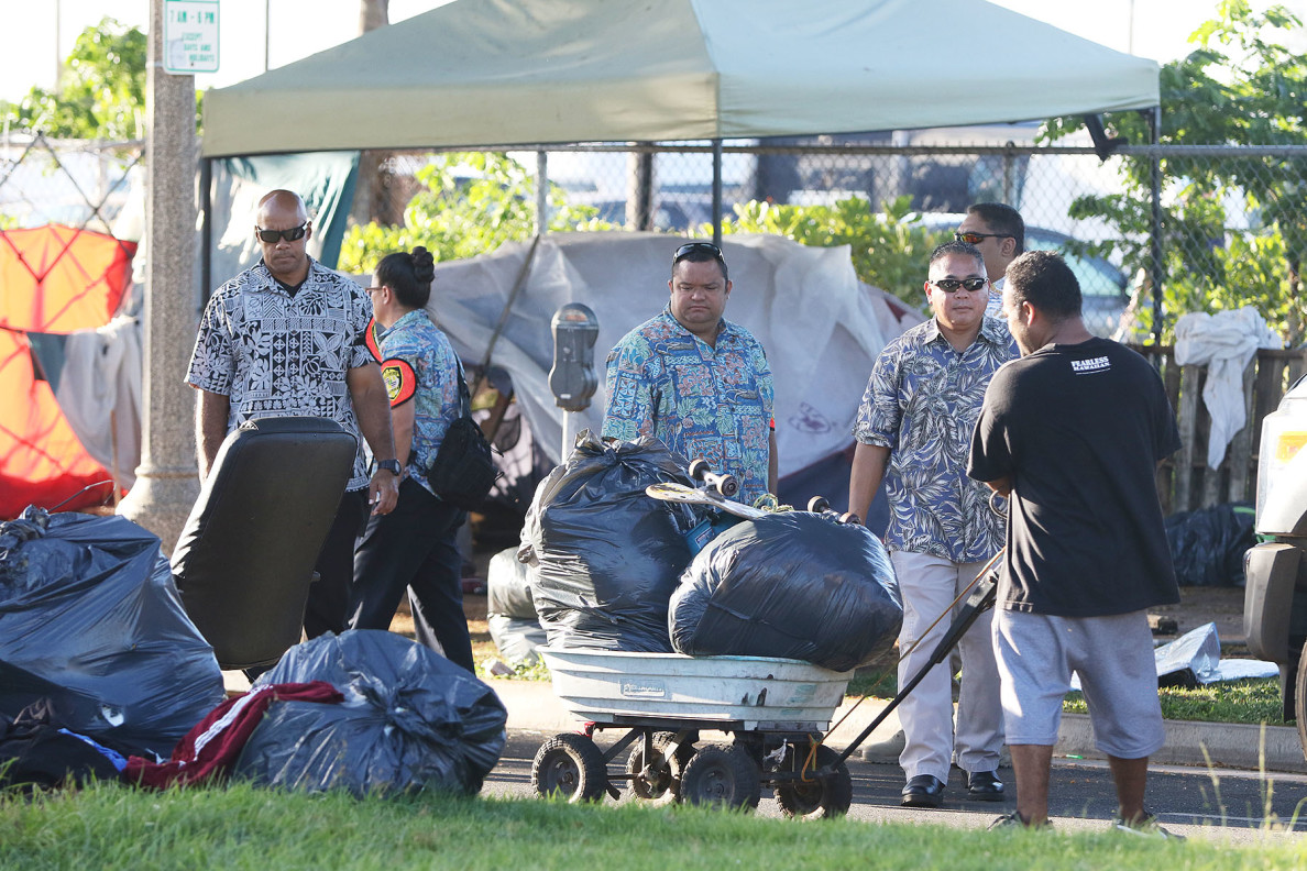 Honolulu Police Department officers stand around as a person hauls belongings along Ilalo Street as city workers sweep and load debris, tents and other trash into a waiting trash truck. 8 oct 2015. photograph Cory Lum/Civil Beat