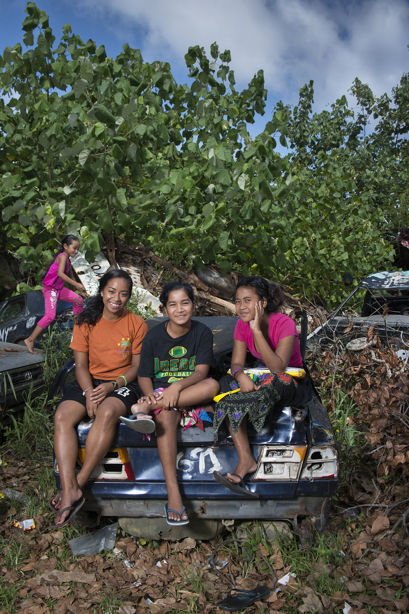 <p>Along the road to Xavier High School on Chuuk, girls pass the time on a rusted car.</p>