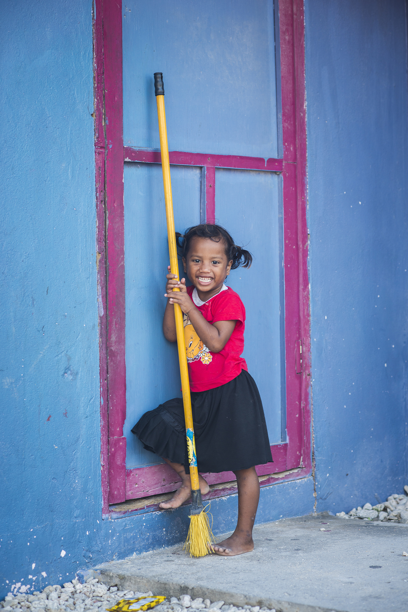 <p>A girl on Ebeye has a happy moment playing with a broom.</p>
