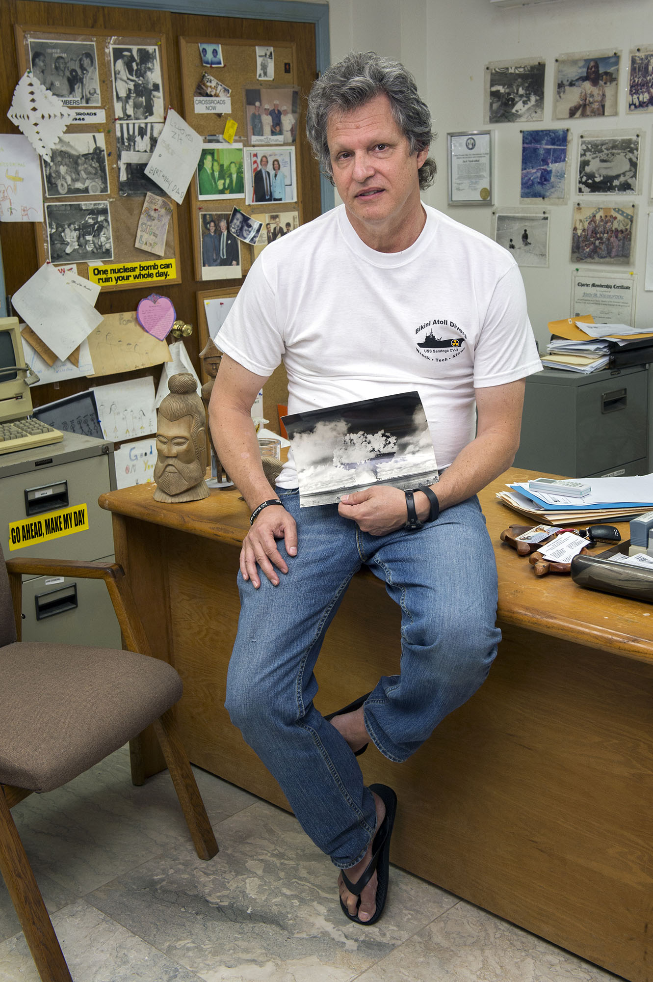 <p>Jack Niedenthal, the Bikini liaison, in his Majuro office, holding a photo of one of the U.S. nuclear explosions in the atoll.</p>