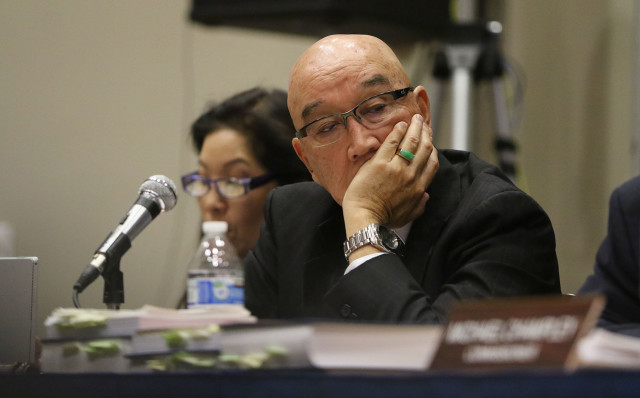 Public Utility Commission Chair Randy Iwase, seen here listening to testimony in November on the NextEra Energy-Hawaiian Electric Industries merger, would have to get one of the other two commissioners to approve hiring or firing executive officers under a bill that lawmakers have introduced this session.