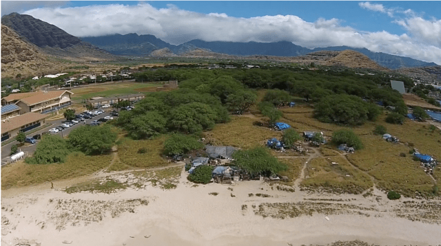 More than 200 people live in tents and makeshift homes on state land between the Waianae Boat Harbor and Waianae High School.