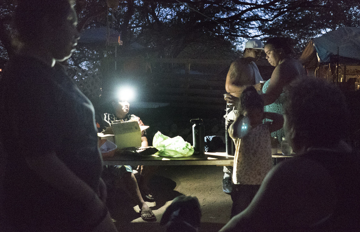 Right, Twinkle and her 'family' sit outside her compound/camp area. Waianae Boat Harbor camp. 10 oct 2015. photograph Cory Lum/Civil Beat