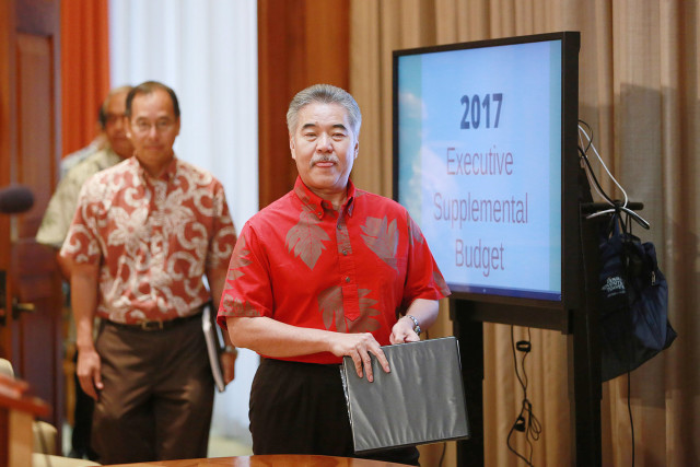 Governor David Ige walks past a monitor in his office before press conference announcing teh 2017 Executive Supplemental Budget at the Capitol. 21 dec 2015. photograph Cory Lum/Civil Beat