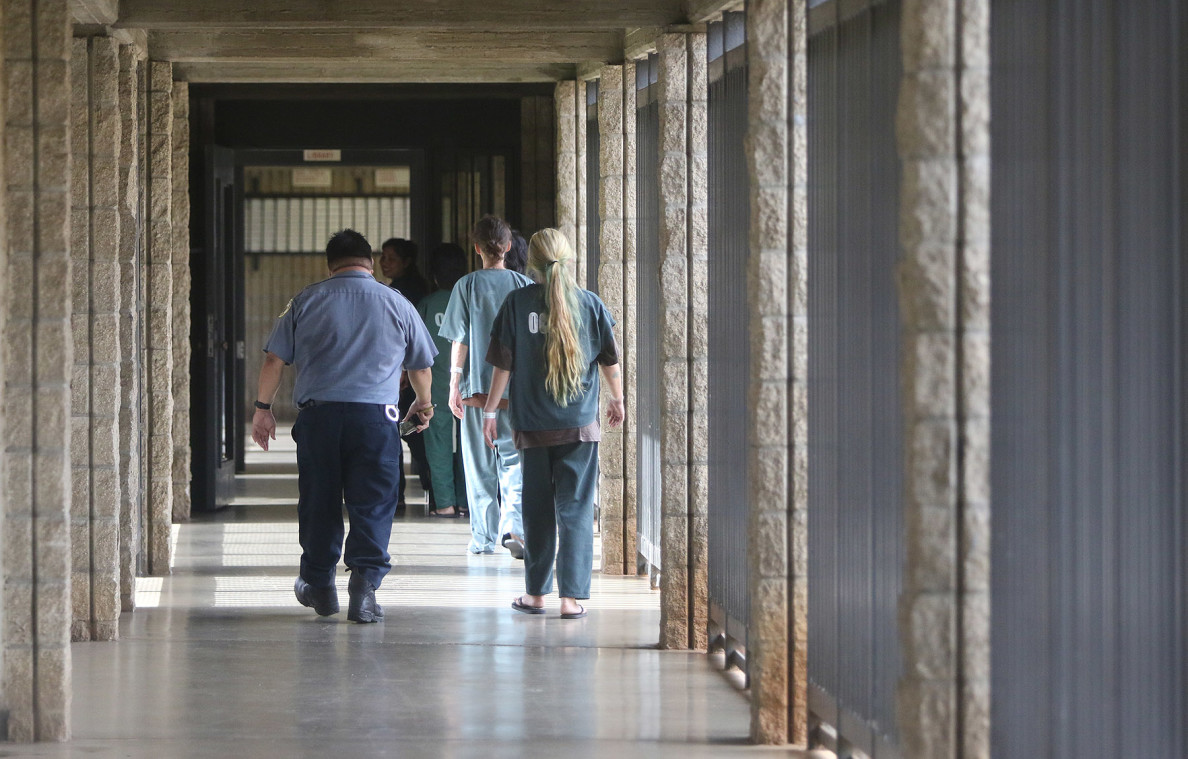 Staff and inmates walk a hall within the Oahu Community Correctional Center in Honolulu.