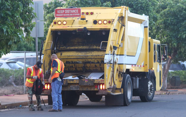 City and County workers separate a backpack found on Ohe Street after a group of independent State of Hawaii contractor/workers hired to handle some of trash went through from the mauka end of Ohe Street picking up cardboard, coconuts and other trash just after 5am. 22 dec 2015. photograph Cory Lum/Civil Beat