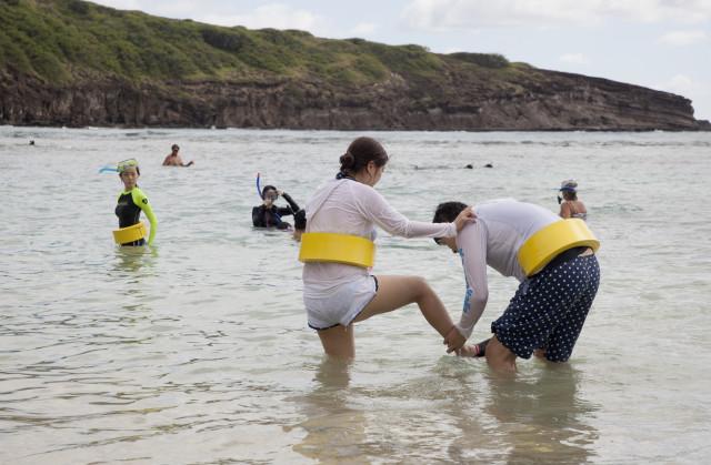 Visitors struggle to take off their snorkeling gear at Hanauma Bay.