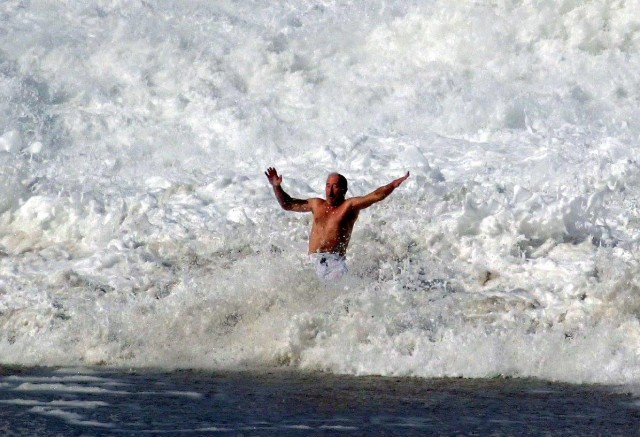 A wave crashes around a man Wednesday at Lumahai Beach.