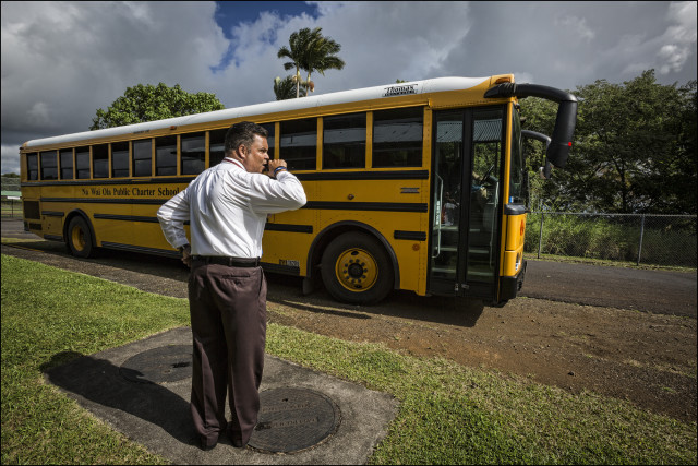 Principal Daniel J. Caluya radios that it's all clear and time to move the bus at the end of the school day at Na Wai Ola Public Charter School.