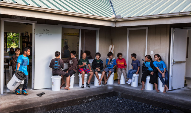 Students multipurpose the barrels as chairs and storage at the Ka 'Umeke Ka'eo charter school in Hilo HI. Students wait outside to go into their next classroom.