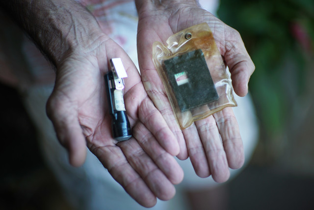Ken Kasik holds two radiation meter devices. The one at right is called a film badge, with the indicator showing red due to exposure to radiation. On the left is a dosimeter, an internal vial switched out daily.