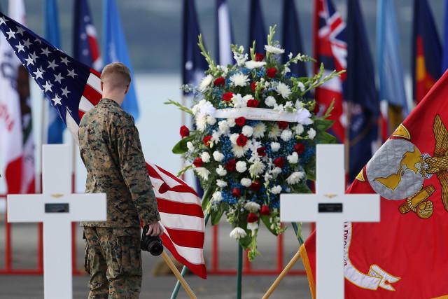 Marine walks near the tarmac fronting crosses and flowers at Marine Corps Base Hawaii. Kaneohe.
