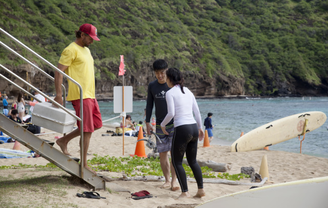 Lifeguard Josh Guerra helps a visitor who cut his foot.