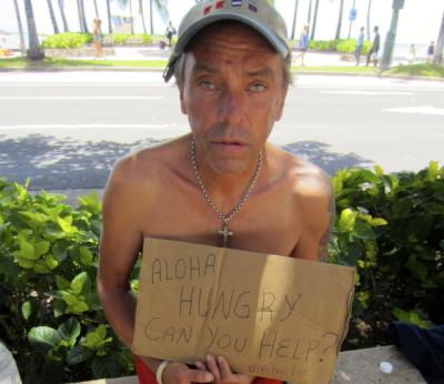 A homeless man panhandles in Waikiki.