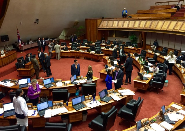 House lawmakers confer Tuesday during one of a dozen breaks they took during a floor session in which they voted on hundreds of bills.