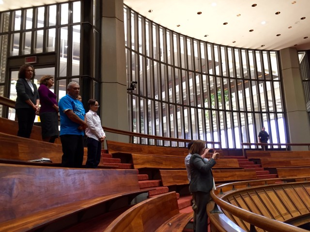 """Hawaiian Home Lands Deputy Director William Aila, left in blue shirt, stands while the House begins its floor session Tuesday with """"Hawaii Pono'i."""""""