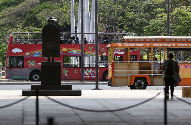 Double decker tour bus and trolley pulled up with visitors fronting the Capitol building and Saint Damien Statue along Beretania Street. 13 april 2016.