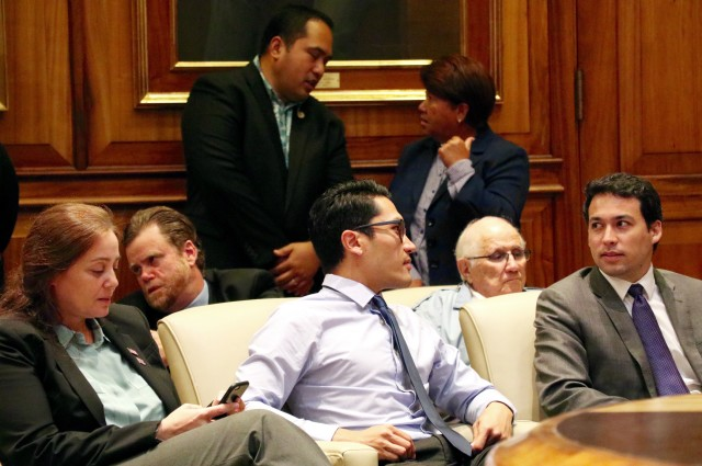 Rep. Kaniela Ing, center, talks to Rep. Chris Lee, far right, as Rep. Nicole Lowen, left, House Speaker Joe Souki and other lawmakers wait in the governor's office for Gov. David Ige to make his announcement about the DHHL funding.