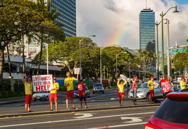 Honolulu lifeguards waved signs in support of their Maui brethren, Monday, at the intersection of Ala Moana Boulevard and Atkinson Drive.
